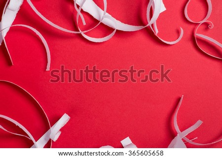 Pieces of white torn paper over the red background - stock photo