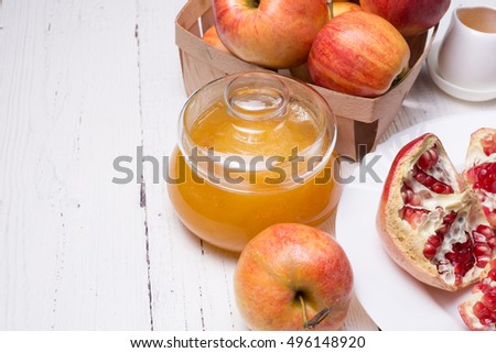 Pieces ripe pomegranate, honey and apple on a white wooden background