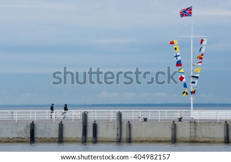 pier and a flagpole with a lot of flags
