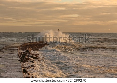 Pier and beacon of Ave river mouth, Vila do Conde, Portugal, in a stormy evening - stock photo