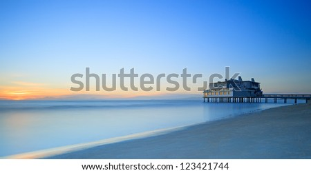 Pier and building on sea water and beach. Panoramic long exposure photography in Follonica travel destination, Maremma, Tuscany, Italy, Europe - stock photo
