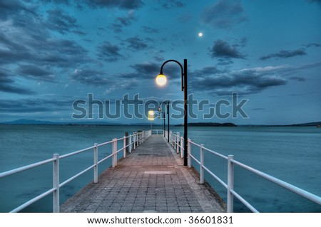 Pier at lake at dawn - stock photo