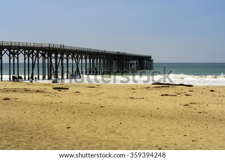 Pier at the beach, golden sand blue sky and ocean with waves crashing into shore.