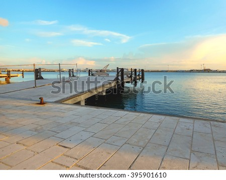 Pier at the port into the sunset - stock photo