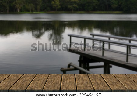 pier at the waterside of the pond in the park in the evening (blur background with wood table top for display or montage your product)