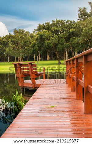 Pier / dock into lake pond with trees field grass and storm clouds on horizon and in reflection looking serene peaceful relaxing rural isolated secluded