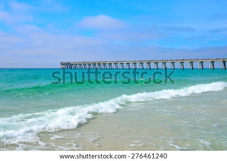 Pier extending out over the blue green ocean at Panama City, FL, USA - stock photo
