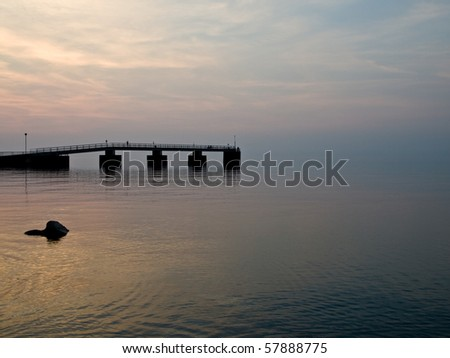Pier jutting out into a calm Lake - stock photo