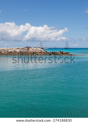 Pier of natural granite stones, beautiful turquoise sea and yachts away on the island of La Digue, Seychelles