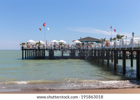 Pier on a sea with comfortable white armchairs - stock photo
