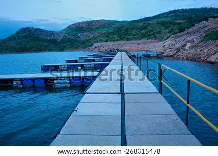 Pier on lake in dusk. Shot on Paris Dam, South Africa.  - stock photo