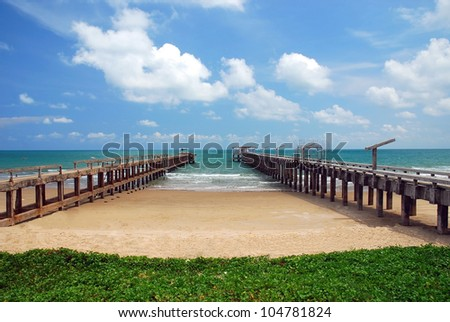 Pier on the beach blue sky and clouds - stock photo
