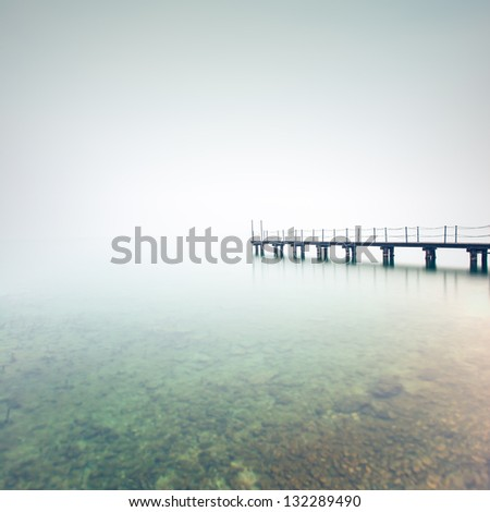 Pier or jetty silhouette in a foggy lake. Garda lake, Italy, Europe - stock photo