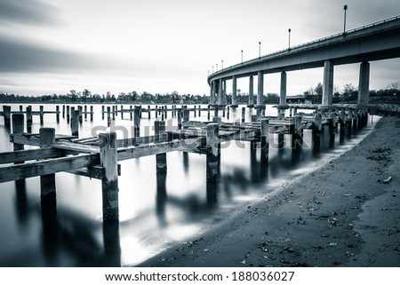 Pier posts in the Severn River and the Naval Academy Bridge, in Annapolis, Maryland.