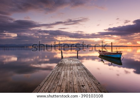 Pier with fishing vessels at sunset - perfectly calm sea with the sky reflected  - stock photo