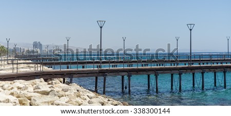Pier with lamp and rails in Mediterranean against distant view on Limassol city. Cyprus.  - stock photo