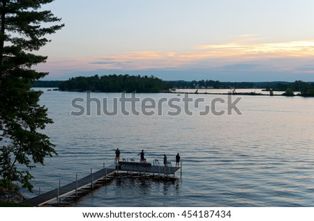 pier with people fishing as sun sets over steamboat bay and birch island of east gull lake in cass county minnesota outside brainerd baxter  - stock photo