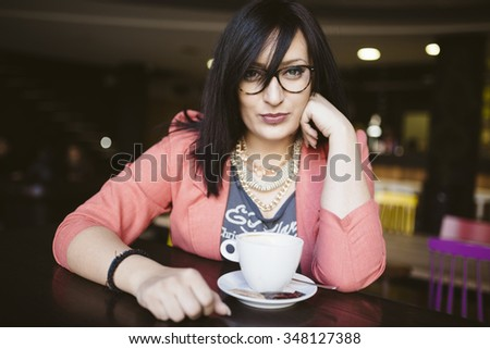 pierced girl drinking coffee in coffee shop