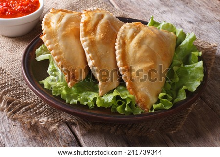 pies empanadas on a plate with lettuce and sauce closeup. horizontal  - stock photo