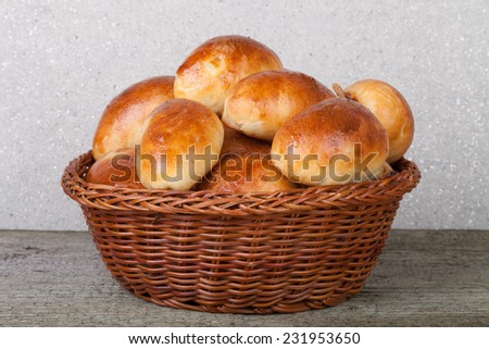 pies with meat or cabbage in a wicker basket on a wooden background. - stock photo