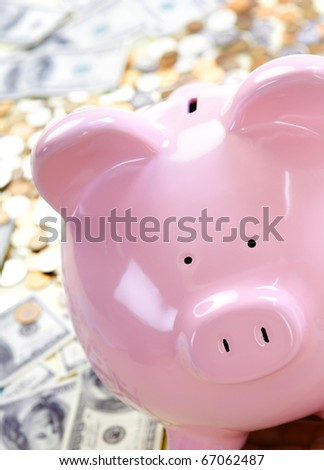 Pig bank and a lot of money coin and bills. - stock photo