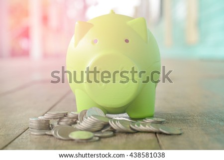 Pig  bank and coin on a wooden floor - stock photo