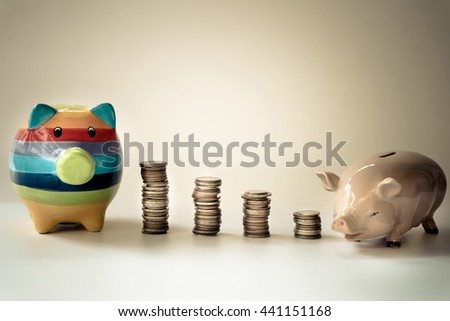 Pig bank for Saving money. Piggy bank savings concept with vintage tone.  Coins with the piggy saving money. Inserting a coin into a piggy bank.