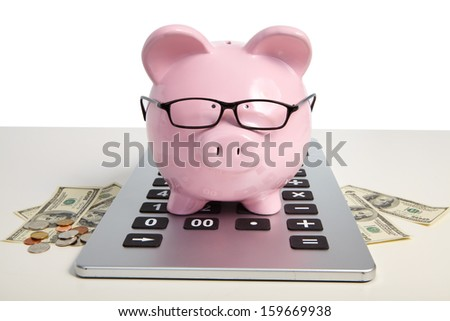 Pig bank on calculator on a white background