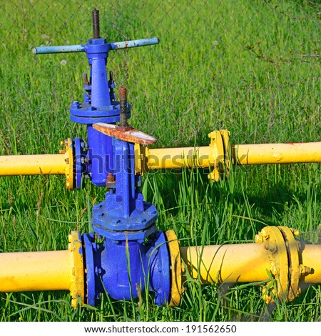 Pig-iron latch on the gas pipeline of low pressure. A pig-iron latch on the gas pipeline of low pressure in an industrial landscape. - stock photo