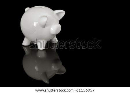 pig shaped money box on a black reflective surface, with space for text