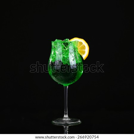 Piggelin Drink, consisting of vodka, melon liqueur and lemon-lime soda. on black background - stock photo