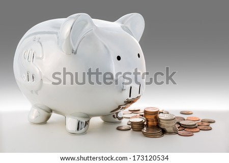 Piggy bank and a pile of coins - stock photo
