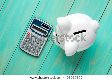 Piggy bank and calculator on the wooden background, top view. - stock photo