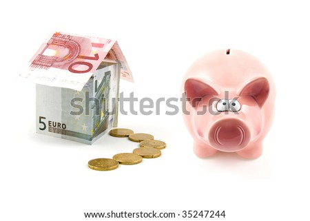 piggy bank and house of banknotes isolated on white background - stock photo