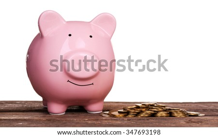 Piggy bank and pile of coins on wooden table against white background