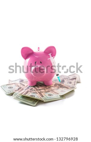 Piggy bank and syringe on a pile of dollars on white background - stock photo