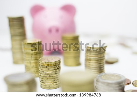 Piggy bank and towers of coins - stock photo