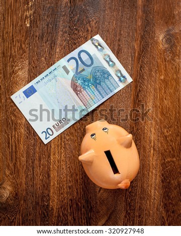 Piggy bank and twenty euro note on brown wooden background. View from top. - stock photo