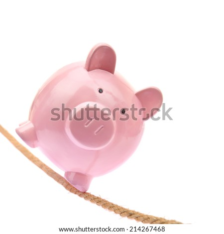 Piggy bank balancing on a rope - stock photo