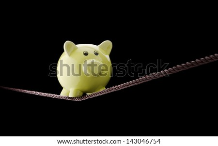 Piggy bank balancing on tightrope - stock photo