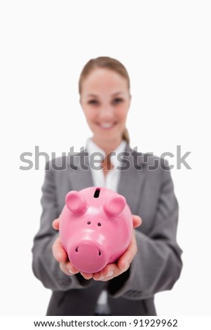 Piggy bank being held by smiling bank employee against a white background - stock photo