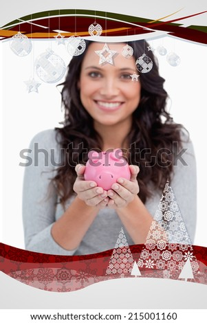 Piggy bank being held by smiling woman against christmas frame - stock photo