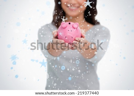 Piggy bank being held by woman against snow falling - stock photo