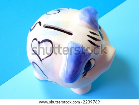 Piggy bank, ceramic money box on blue background - stock photo