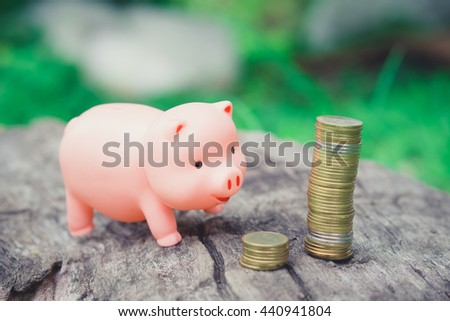 Piggy Bank choosing coin stack on wooden floor.