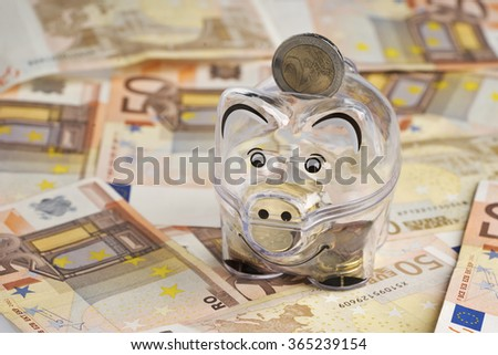 Piggy bank, coins and euro bills. Money saving concept. Banknotes closeup, isolated background. - stock photo