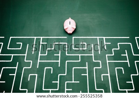Piggy bank entering into a maze. - stock photo