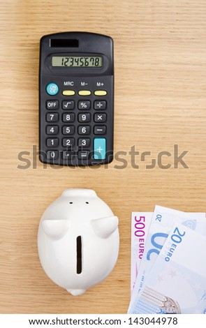 Piggy bank, euro bills and calculator on a table. Top view. - stock photo