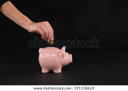 Piggy bank. Female hand putting a coin into piggy bank - stock photo