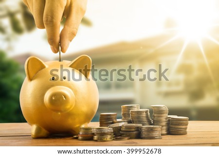 Piggy bank gold color and stack of money with white background. - stock photo